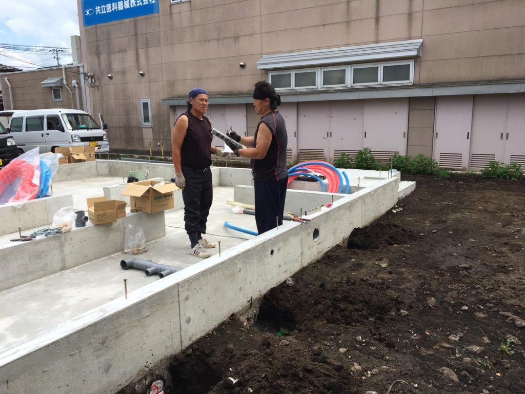 図面を確認中の水道屋さん|八戸市 工務店
